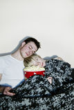 Young couple watching television. Eating a huge bowl of fresh buttered popcorn comfortably wrapped in a blanket. The movie might be a bit boring since both of Stock Photography