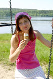 Eating ice cream. Girl on a swing, eating ice cream Royalty Free Stock Photography