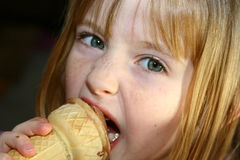 Eating icecream. Young girl eating  a chocolate icecream cone Stock Image