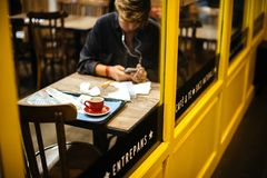 Eating inside Spanish cafe Sandwi CHez working. Barcelona, Spain - Nov 14, 2017: View from the street of Young woman eating inside Spanish cafe Sandwi CHez stock photos