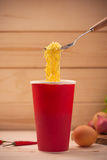 Eating Instant noodles in cup with a fork Stock Photos
