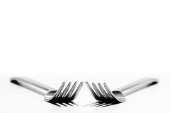 Eating Irons. Two forks angled towards each other white background Royalty Free Stock Photo