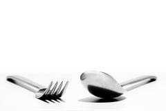 Eating Irons. Fork and spoon angled towards each other white background Stock Images