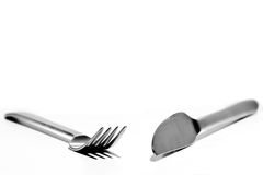 Eating Irons. Fork and knife angled towards each other white background Royalty Free Stock Image