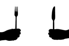 Eating Irons. Fork and knife in fists in silhouette Royalty Free Stock Photo