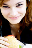 Eating junk food. Pretty girl eating junk food hamburger royalty free stock images