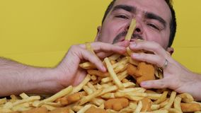 Eating junk food nutrition and dietary health problem concept. Young man eating with two hands a huge amount of unhealthy fast stock video footage