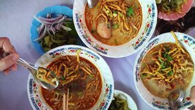 Eating Kaosoi Thai food Northern Thailand Chiang Mai herb and coconut milk noodle