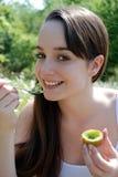 Eating kiwi fruit Royalty Free Stock Photography