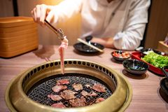 Eating Korean Barbecue buffet in restaurant. Asian man using kitchen tongs grilling beef and bacon on grill plate. Eating Korean Barbecue buffet in the royalty free stock photography