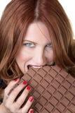 Eating a large chocolate bar Stock Photos