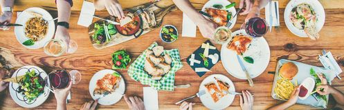 Eating and leisure concept - group of people having dinner at table with food stock photos