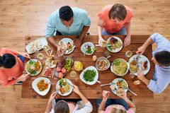 Group of people eating at table with food Stock Photo