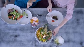 Eating and leisure, top view on girls having dinner and serving salad at table with healthy food and beverages
