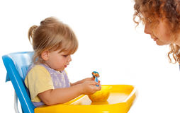 Eating little girl, young woman looking on it Stock Image