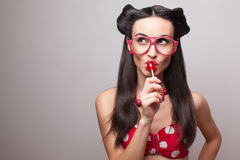 Eating lollipop. Pin Up styling girl eating lollipop royalty free stock photography
