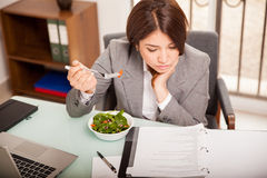 Eating lunch at the office. Busy young business woman eating a healthy lunch while working in her office stock images