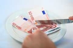 Eating money. Two hands about to cut two 10 Euro bills on a plate with knife and fork, depicting high cost of food Royalty Free Stock Photography