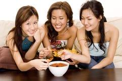 Eating Nachos #1. Three women dipping nachos into a salsa sauce Royalty Free Stock Photos