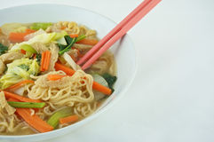 Eating noodle and clear soup vegetarian. Egg noodle and clear soup vegetarian for health. It include vegan protein dry, carrot, kale and cabbage on white Stock Image