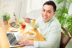 Eating noodle. Young Asian office worker eating instant noodle while working on laptop Stock Photography