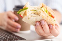 Eating in the office. With sandwich stock photography