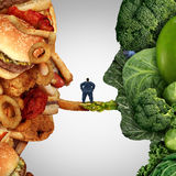 Eating Options. Food health issue as an obese man standing on a bridge between junk food and fruit and vegetable group shaped as a human head as a concept for Royalty Free Stock Photos