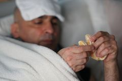 Eating an orange to assume vitamin C. Sick man lying in bed eating an orange to get vitamin C. Selective focus stock photos