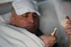 Eating an orange to assume vitamin C. Sick man lying in bed eating an orange to get vitamin C. Selective focus Royalty Free Stock Image