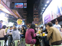 Eating at an Outdoor Night Market. MARCH 2013 - HONG KONG: People eat outside at the Temple Street night market in Hong Kong Royalty Free Stock Image