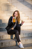 Eating outdoor - woman with sandwich and juice on stairs Stock Image