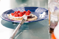 Eating pancakes dessert with raspberry, cream and chocolate crea Stock Photos