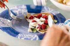 Eating pancakes dessert with raspberry, kiwi, banana and cream. Eating pancakes dessert with raspberry Stock Photos