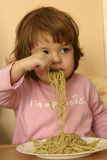 Eating pasta. Little child eating pasta with pesto sauce Royalty Free Stock Photography