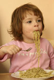 Eating pasta. Little child eating pasta with pesto sauce Stock Photos