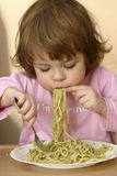 Eating pasta. Little child eating pasta with pesto sauce Stock Image