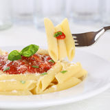Eating pasta Rigate Napoli with tomato sauce with fork Royalty Free Stock Image