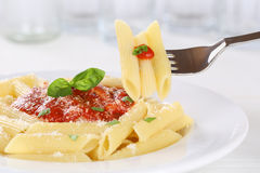 Eating pasta Rigate Napoli with tomato sauce noodles on fork Royalty Free Stock Photography