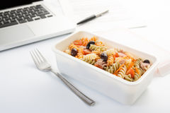 Eating a pasta salad in the office. Eating a pasta salad with vegetables and tuna in the office stock images