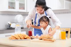 eating and people concept - Asian happy mother and daughter having breakfast at home. stock images