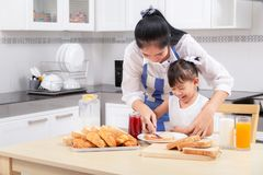 Eating and people concept - Asian happy mother and daughter havi. Ng breakfast at home stock photos