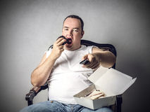 Eating a piece of cake in front of the tv Stock Photos