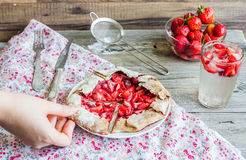Eating a piece of rye biscuit with fresh strawberries, summer pi Stock Images