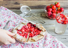 Eating a piece of rye biscuit with fresh strawberries, summer pi Royalty Free Stock Photos