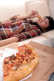 Eating pizza. Young woman lie down on sofa and eating pizza Stock Images