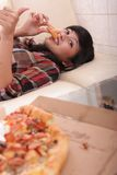 Eating pizza. Young woman lie down on sofa and eating pizza Stock Photos