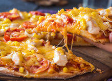 Eating pizza with chicken, corn, tomatoes and cheese double, han Stock Images