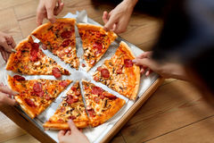 Eating Pizza. Group Of Friends Sharing Pizza. Fast Food, Leisure. Eating Pizza. Group Of Friends Sharing Pizza Together. People Hands Taking Slices Of Pepperoni Royalty Free Stock Photos