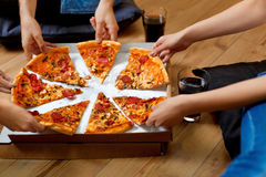 Eating Pizza. Group Of Friends Sharing Pizza. Fast Food, Leisure. Eating Pizza. Group Of Friends Sharing Pizza Together. People Hands Taking Slices Of Pepperoni Stock Photography