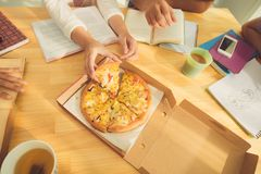 Eating pizza. Hands of students eating pizza while preparing for exam, view from above Royalty Free Stock Photos